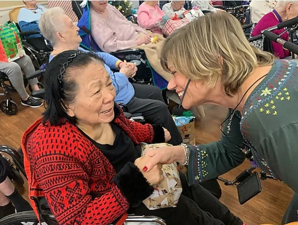 A Bridgeway Senior Healthcare activities director greets a resident during a holiday event.
